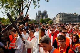 With Notre Dame cathedral in background, religious officials carry the cross during the Good Friday procession, in Paris, Apr. 19, 2019.