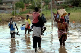 People cross a section of Pemba, a city that remains flooded on the northeastern coast of Mozambique, May, 2, 2019.