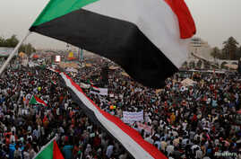 Thousands of protesters wave Sudanese flags, hold banners and chant slogans during a demonstration in front of the Defense Ministry in Khartoum, Sudan, April 18, 2019.