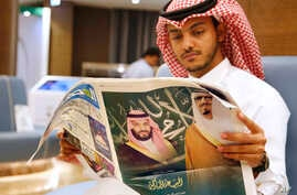 A man reads a newspaper with pictures of Saudi King Salman, right, and his Crown Prince Mohammed bin Salman, at the press center for the upcoming Arab and Islamic summits in Mecca, Saudi Arabia, Thursday, May 30, 2019. King Salman convenes Arab heads of state from the Gulf and Arab League to discuss escalation in tension with Iran. (AP Photo/Amr Nabil)