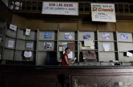 FILE - In this Oct. 9, 2009, photo, an employee works in a government food store with empty shelves in Havana, Cuba. The Cuban government said on May 10, 2019, that it would begin rationing chicken, eggs, rice, beans, soap and other basic products in...