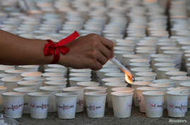 FILE - A campaign supporter lights candles in the Philippines as part of commemorations of International AIDS Candlelight Memorial Day in Quezon city, metro Manila, the Philippines, May 14, 2016.