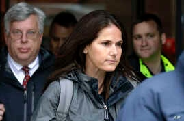Former University of Southern California soccer coach Laura Janke departs federal court, May 14, 2019, in Boston, where she pleaded guilty to charges in a nationwide college admissions bribery scandal.