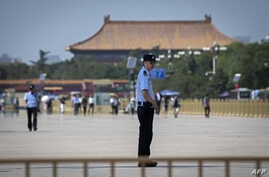 Police officers patrol and secure an area on Tiananmen Square in Beijing on June 3, 2019.  (Photo by Nicolas ASFOURI / AFP)