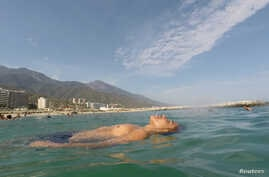FILE - Victor floats in the sea as he spends a day at Coral beach, La Guaira, near Caracas, Venezuela, March 23, 2019.