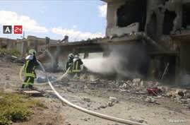 FILE - Firefighters respond at the destroyed building of Nabd Al-Hayat hospital that was hit by an airstrike in Hass, Idlib province, Syria, May 6, 2019, in this still image taken from a video on May 9, 2019.