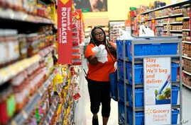 FILE - In this Nov. 9, 2018, photo, Walmart associate Alicia Carter fulfills online grocery orders at a Walmart Supercenter in Houston. Amazon and Walmart on April 18, 2019, are kicking off a two-year pilot established by the government to allow low-...
