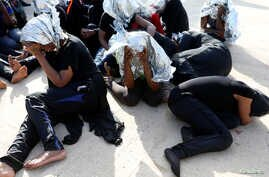 Migrants sit at a naval base after being rescued by Libyan coast guards in Tripoli, Libya J