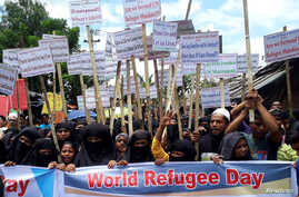 Rohingya refugees hold placards as they participate in a rally to observe World Refugee Day at the Rohingya refugee camp in Cox'