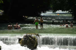 People swim in the Eisbach river that runs through the English Garden in Munich, Germany, June 26, 2019.