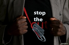 "FILE - A man shows the logo of a T-shirt that reads ""Stop the Cut"" referring to Female Genital Mutilation (FGM) during a social event advocating against harmful practices such as FGM at the Imbirikani Girls High School in Imbirikani, Kenya, April 21, 2016."