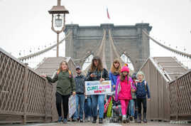 Climate change activist Zayne Cowie and his mother Eve Mosher walk on the Brooklyn Bridge during a youth climate march in NY