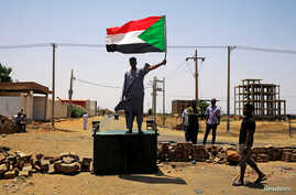 FILE - A Sudanese protester holds a national flag as he stands on a barricade along a street, in Khartoum, Sudan, June 5, 2019.