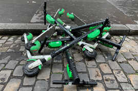FILE - Dock-free electric scooters Lime-S by California-based bicycle sharing service Lime are stacked on Parisian cobblestones in a street of Paris, France, May 19, 2019. Picture taken May 19, 2019.