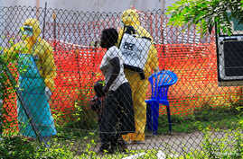 A woman and her child arrive for an Ebola-related investigation at the health facility at the Bwera hospital near the border with the Democratic Republic of Congo in Bwera, Uganda, June 14, 2019.