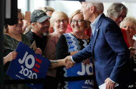 Democratic presidential candidate and former Vice President Joe Biden shakes hands as he arrives for a town hall meeting, in Ottumwa, Iowa, June 11, 2019.