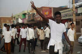 A protester flashes the victory sign, as others block a road during a protest, in Khartoum, Sudan, June 24, 2019.