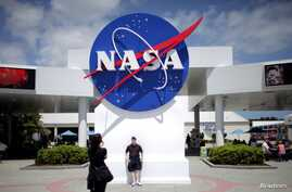 FILE - Tourists take pictures of a NASA sign at the Kennedy Space Center visitors complex in Cape Canaveral, Fla.