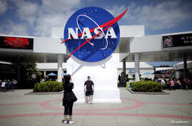 Tourists take pictures of a NASA sign at the Kennedy Space Center visitors complex in Cape Canaveral, Florida, April 14, 2010.