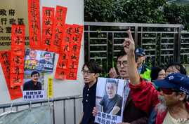 """FILE - Hong Kong pro-democracy activists hold a placard, at right, that reads """"rights activism is not wrong, free Huang Qi"""" during a protest outside the Chinese Liaison Office in Hong Kong, Jan. 29, 2019."""