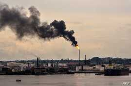 FILE - Black smoke billows from the chimney of an oil refinery in Havana, Cuba, June 5, 2017.