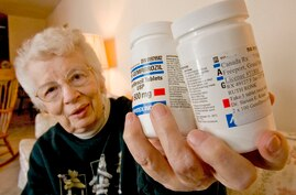 FILE - Ruth Ronk holds some of the medications she has purchased from Canada, in her Appleton, Wis. home.