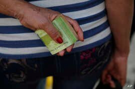 FILE - A woman holds a wad of bills to pay her bus fare in Caracas, Venezuela, Feb. 7, 2018.