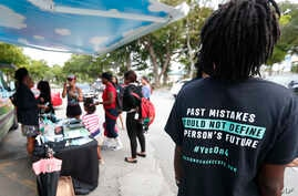"""FILE -  people gather around the Ben & Jerry's """"Yes on 4"""" truck as they learn about Amendment 4 and eat free ice cream at Charles Hadley Park in Miami."""