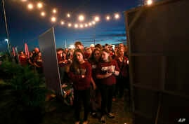 Attendees look at a memorial for the victims of the Parkland, Fla., shooting, after an interfaith service, Thursday, Feb. 14, 20
