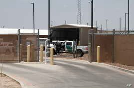 FILE - A Customs and Border Patrol officer guards the entrance to the Border Patrol station in Clint, Texas.