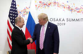 U.S. President Donald Trump, right, and Russian President Vladimir Putin greet each other during a bilateral meeting.
