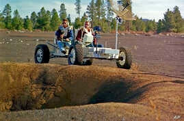 Undated photo provided by the U.S. Geological Survey Astrogeology Science Center shows Apollo 15 astronauts Jim Irwin (L), and Dave Scott driving a prototype of a lunar rover in a volcanic cinder field east of Flagstaff, Ariz.