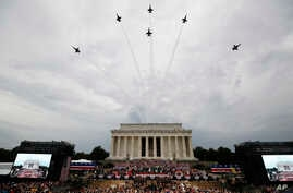 President Donald Trump, first lady Melania Trump, Vice President Mike Pence and Karen Pence and others stand as the US Army Band performs and the US Navy Blue Angels flyover at the end of an Independence Day celebration in front of the Lincoln Memorial, July 4, 2019, in Washington.