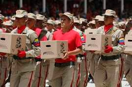 FILE - Bolivarian militiamen hold boxes of subsidized food for distribution under a government program during an Independence Day parade in Caracas, Venezuela, July 5, 2019.