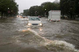 Heavy rainfall flooded the intersection of 15th Street and Constitution Ave., NW, stalling cars in the street, July 8, 2019, in Washington.