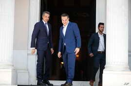 Greece's newly-elected prime minister Kyriakos Mitsotakis (L) looks on as outgoing prime minister Alexis Tsipras, center,leaves the Maximos Mansion in Athens,, July 8, 2019.