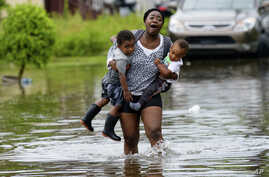 Terrian Jones reacts as she feels something moving in the floodwater at her feet as she carries Drew and Chance Furlough to their mother on Belfast Street in New Orleans, July 10, 2019.