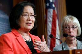 Sen. Mazie Hirono, D-Hawaii (L) holds back tears as she recalls images of drowned migrants during a news conference on new legislation regarding detention of immigrants n the southern border, July 11, 2019, Capitol Hill, Washington.
