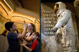 Some of the first visitors  to view Neil Armstrong's Apollo 11 spacesuit after it is unveiled at the Smithsonian's National Air and Space Museum in Washington, July 16, 2019, take photos of the suit.