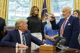 President Donald Trump listens to Apollo 11 astronaut Buzz Aldrin, right, with Vice first lady Melania Trump, during a photo opportunity commemorating the 50th anniversary of the Apollo 11 moon landing in the Oval Office of the White House, Friday, July 19, 2019, in Washington.