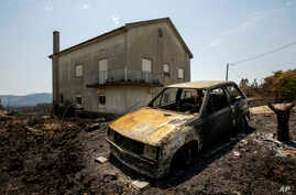 A burnt car is seen following a fire near Roda, in central Portugal on July 23, 2019. Emergency services in Portugal have brought under control a huge wildfire which raged for four days and injured 39 people.