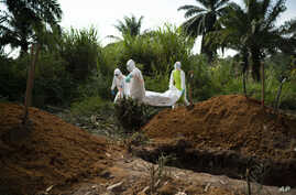 Workers bury the remains of Mussa Kathembo, an Islamic scholar who had prayed over those who were sick in Beni, Congo, July 14, 2019. Kathembo himself died of Ebola.