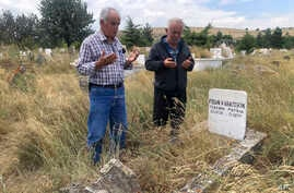 Adem Karaagac, left, and Satilmis Karatekin pray at the grave of a distant relative of Boris Johnson, in Kalfat, a village in the Cankiri province, 100 kilometers (62 miles) north of the Turkish capital Ankara, Turkey, July 25, 2019.