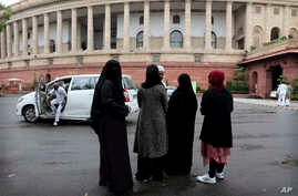 Indian Muslims stand outside Parliament House in New Delhi, India, Friday, July 26, 2019.