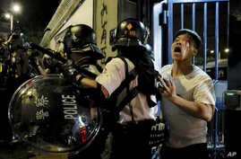 A bleeding man is taken away by policemen after attacked by protesters outside Kwai Chung police station in Hong Kong, Wednesday, July 31, 2019.