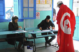 FILE - A Tunisian draped in the national flag arrives at a polling station to vote in La Marsa, outskirts of Tunis, Tunisia, Dec, 21, 2014.
