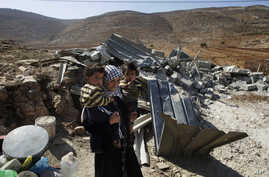 FILE - A Palestinian woman carries her children after the destruction of her home in Aqraba village, near the settlement of Itamar, Nablus, West Bank.