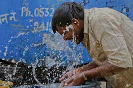 FILE - An Indian worker splashes water on his face as he tries to cool himself on a hot summer day in Allahabad, India.
