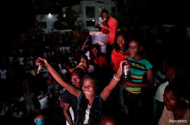 A Haitian woman reacts as she watches a television broadcast of the match between Haiti and Canada during the CONCACAF Gold Cup