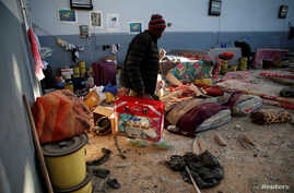 A migrant carries his belongings at a detention center for mainly African migrants, that was hit by an airstrike in the Tajoura suburb of Tripoli, Libya July 3, 2019.